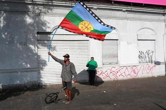 Un manifestante ondea la bandera mapuche durante una protesta contra la visita del Papa en Santiago (Chile).