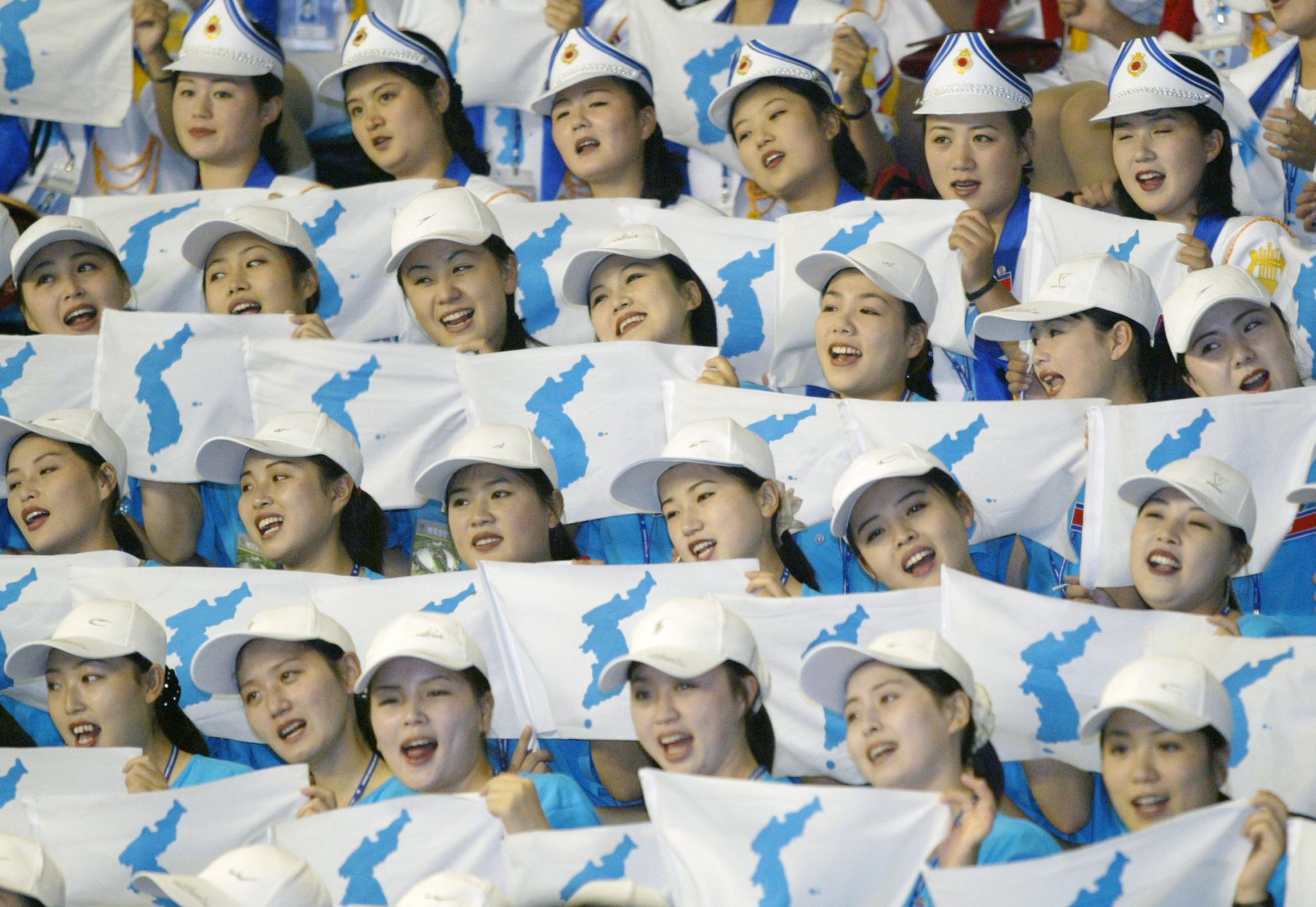 Animadoras norcoreanas apoyan al equipo de volleyball durante un partido contra EEUU.