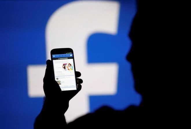 Un usuario consulta Facebook con su teléfono móvil.