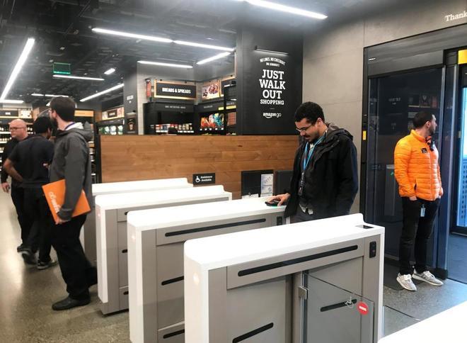 Consumidores escanean sus móviles en el supermercado sin cajas de Amazon.