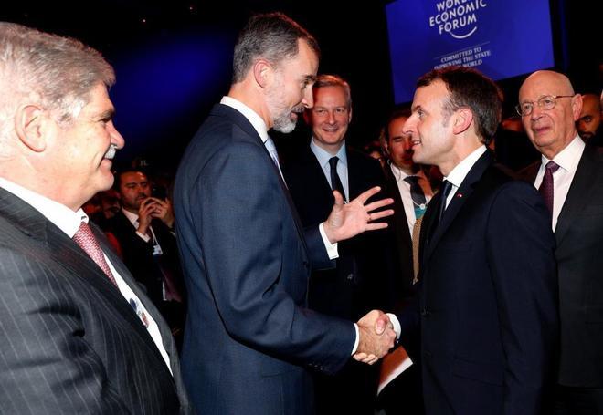 Alfonso Dastis observa el saludo entre Felipe VI y Emmanuel Macron, ayer, en el Foro Económico de Davos (Suiza).