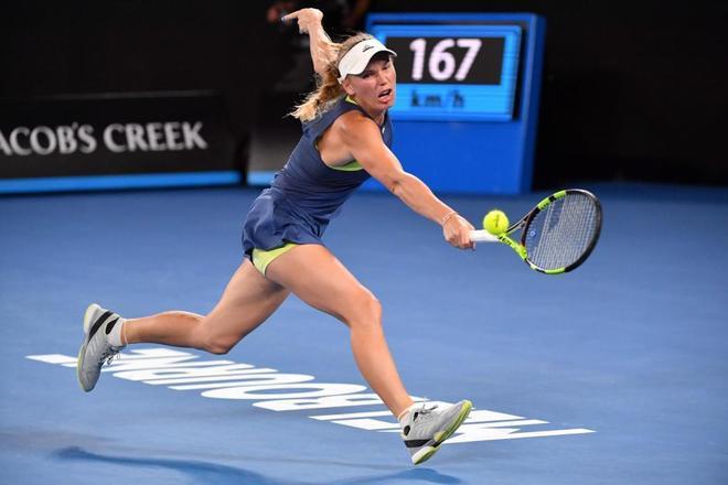 La danesa Caroline Wozniacki se estira para llegar a una bola de...
