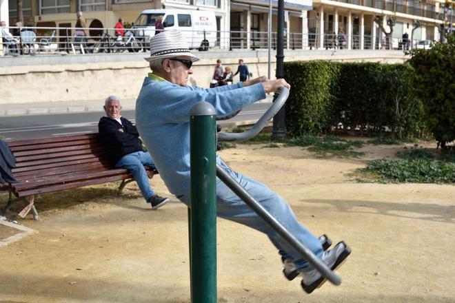 Un jubilado hace ejercicio en un parque frente al puerto de Benidorm.