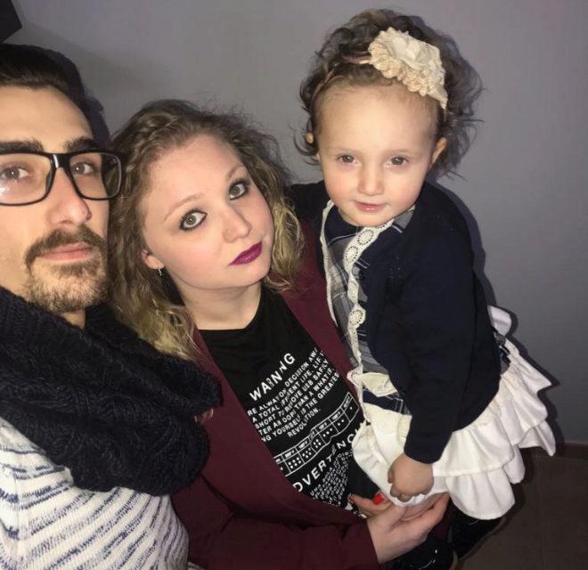 La pequeña Vega, en brazos de sus padres cuando se cumple un año de la operación.