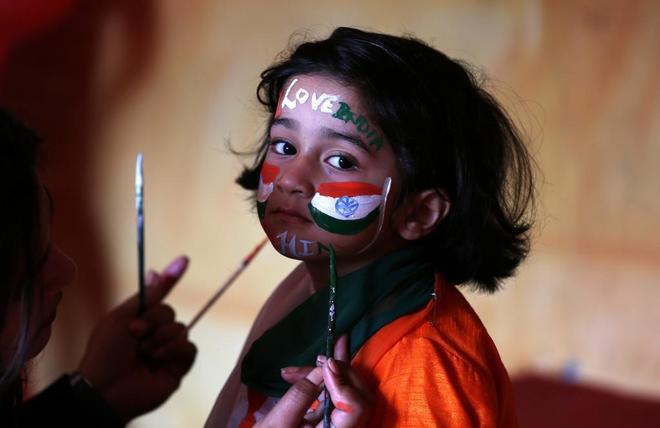 Una niña con la cara pintada con los colores de la bandera de India...