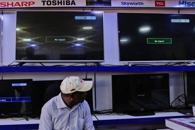 Un hombre sentado junto a varias pantallas de televisión sin señal en una tienda hoy en Nairobi, Kenia