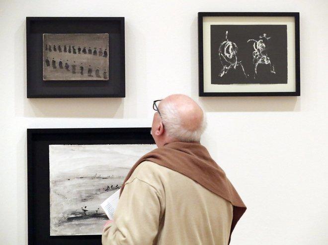 Un hombre observa varias de las pinturas expuestas.