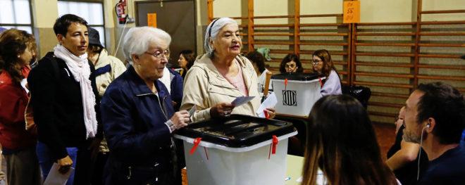 Varias personas depositan esu voto en las urnas del Centre Cívic La...