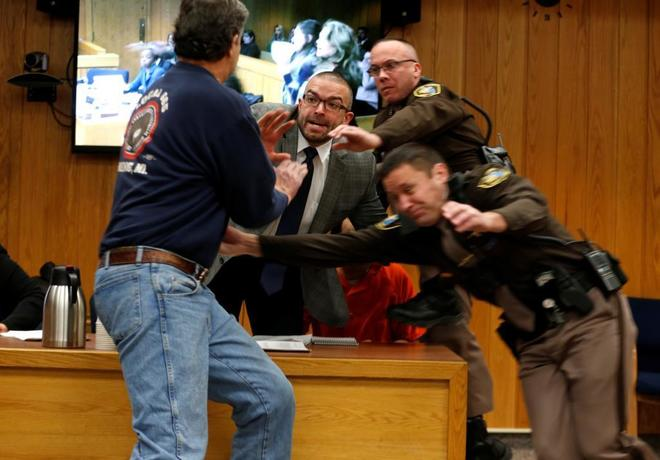 Randall Margraves (i) ataca a Larry Nassar (naranja) durante el juicio.