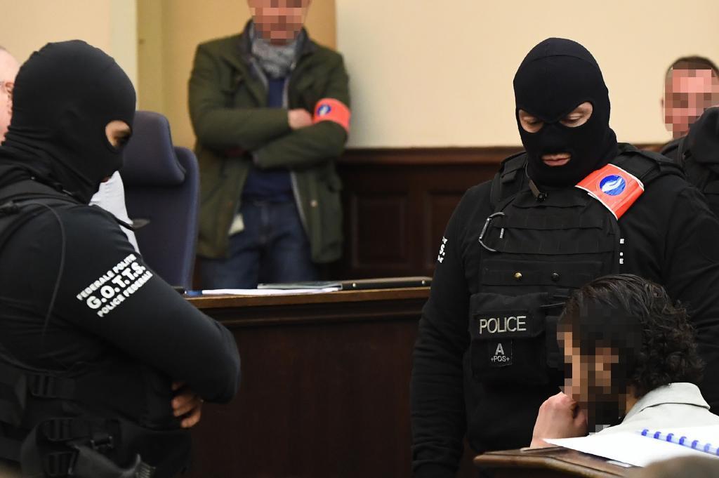 Salah Abdeslam, con la cara pixelada, custodiado por dos policías en la sala del juicio del Palacio de Justicia de Bruselas.
