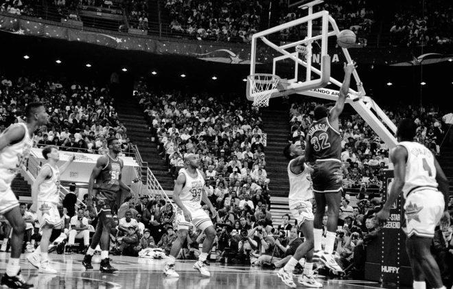 Magic Johnson, defendido por Isiah Thomas, lanza a canasta durante el...