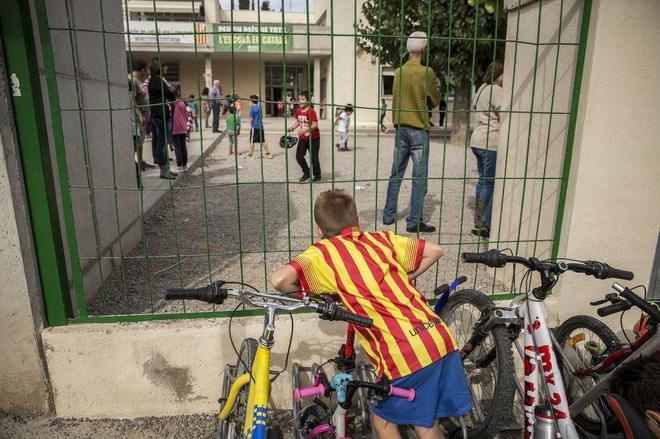 """Al fondo, pancartas en un colegio de Berga que reclaman """"La escuela en catalán ahora y siempre"""" y """"Por un país de todos, la escuela en catalán""""."""