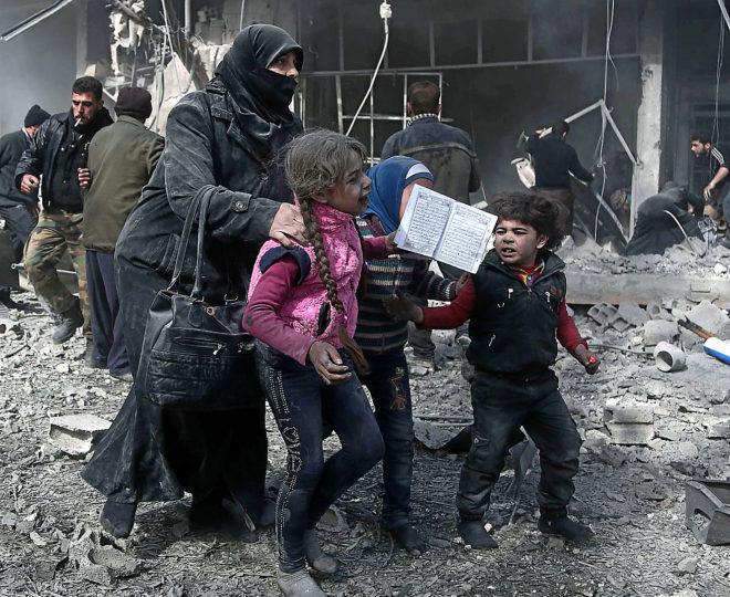 Una mujer siria y varios niños huyen para ponerse a cubierto en Hamouria, Guta.