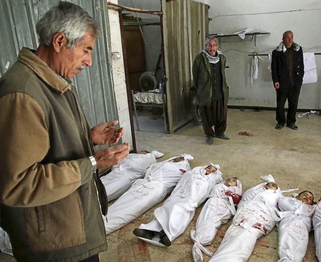 Un hombre sirio reza junto a los cadáveres de varios niños fallecidos.