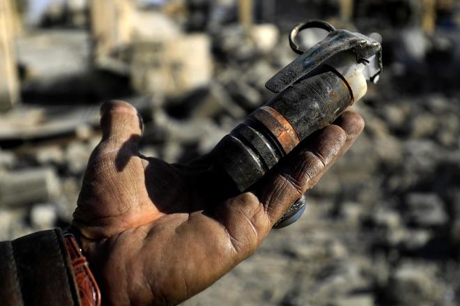 Un hombre sostiene una mina sin detonar que dejó el Estado Islámico en Raqqa (Siria)
