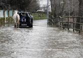 Un joven ayuda a un caballo a pasar por una carretera inundada en...