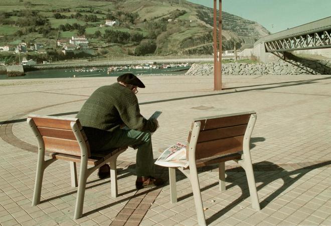 Un pensionista leyendo el periódico en un banco en el País Vasco.