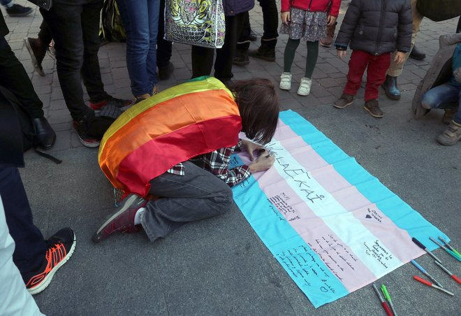 Una joven firma sobre una bandera trans durante la concentración convocada por la Chrysallis.