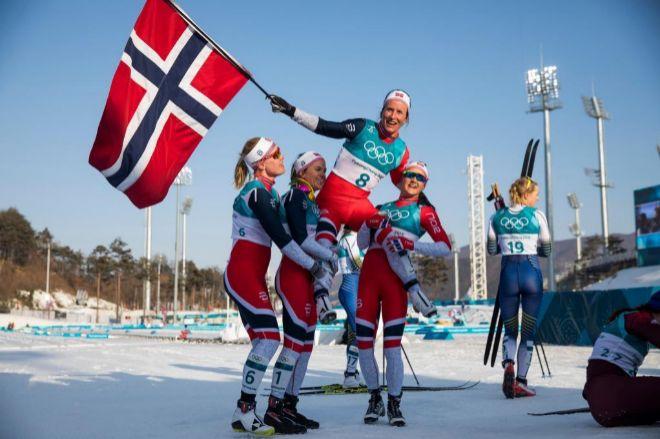 Marit Bjoergen, es levantada por sus compañeras al alzarse con el oro en esquí de fondo.