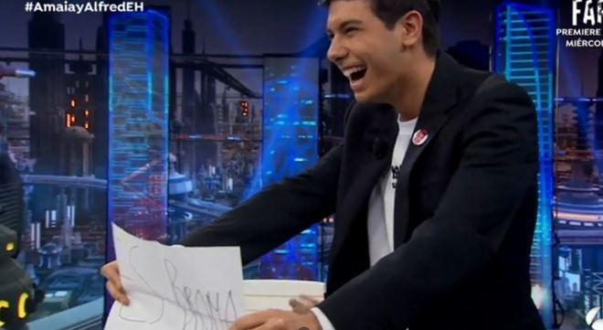 Alfred  muestra el cartel en el que confirma que le han gastado una...