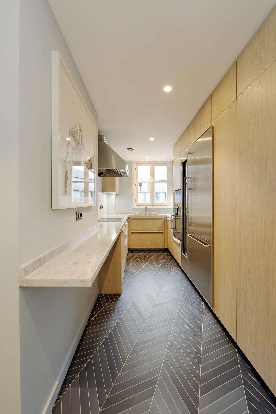 La cocina donde destacan los azulejos gris oscuro del for Suelos laminados en forma de espiga