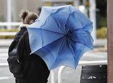 Una mujer intenta que el viento no arrastre su paraguas ayer en...