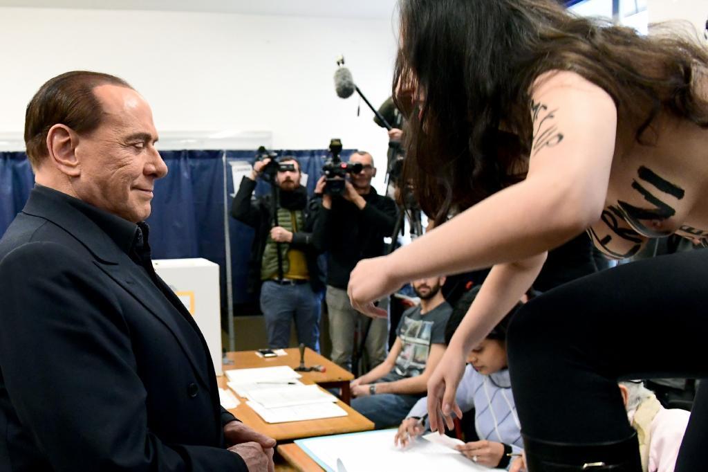 Berlusconi sonríe tras la irrupción de una activista de Femen cuando iba a votar.