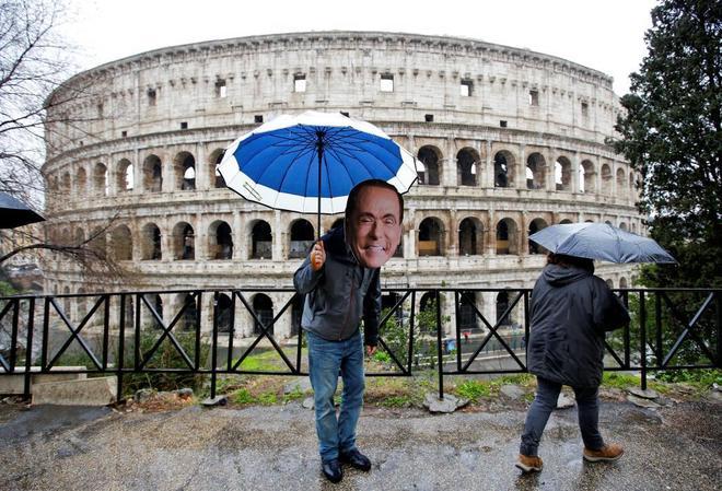 Un activista lleva una máscara de Silvio Berlusconi, frente al Coliseo de Roma.