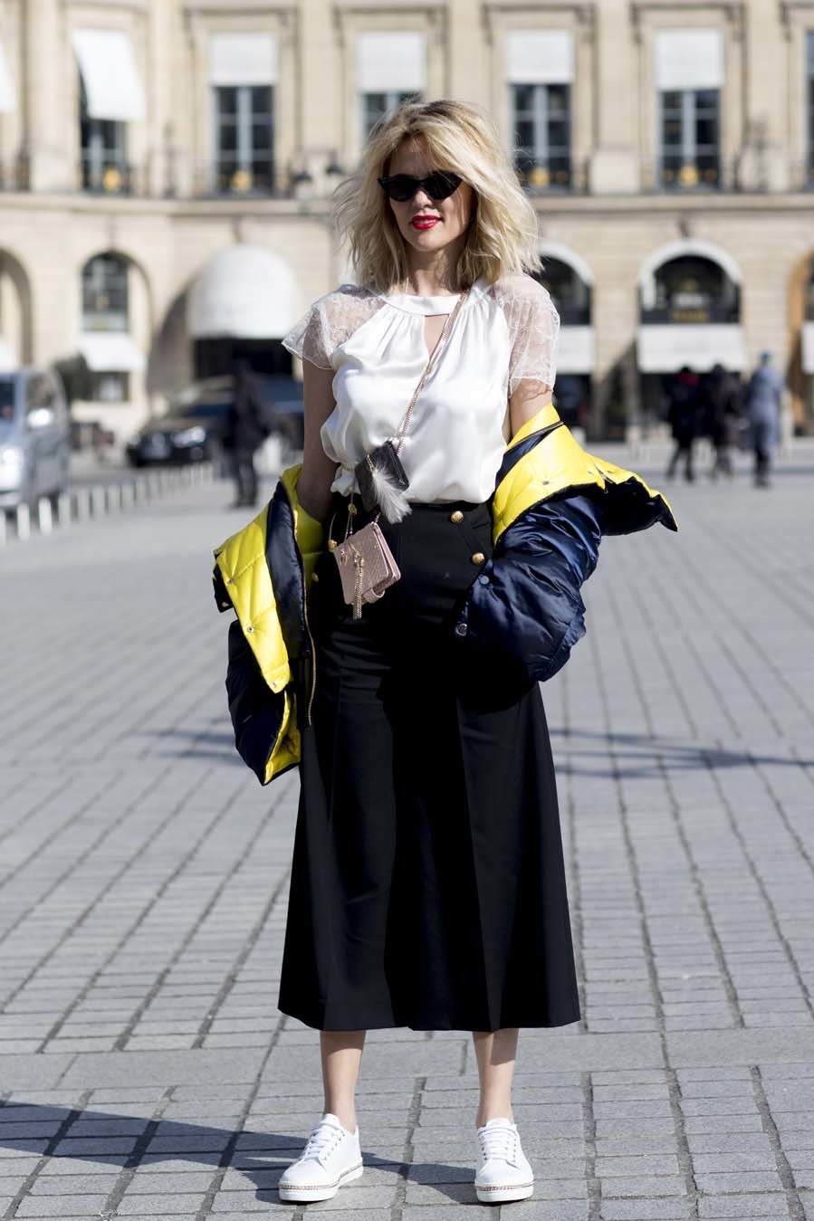 Con falda midi azul marino y blusa con transparencias, dándole un...