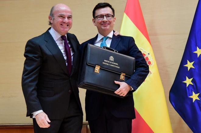 Luis de Guindos, con el nuevo ministro de Economía, Román Escolano, tras el traspaso de cartera.