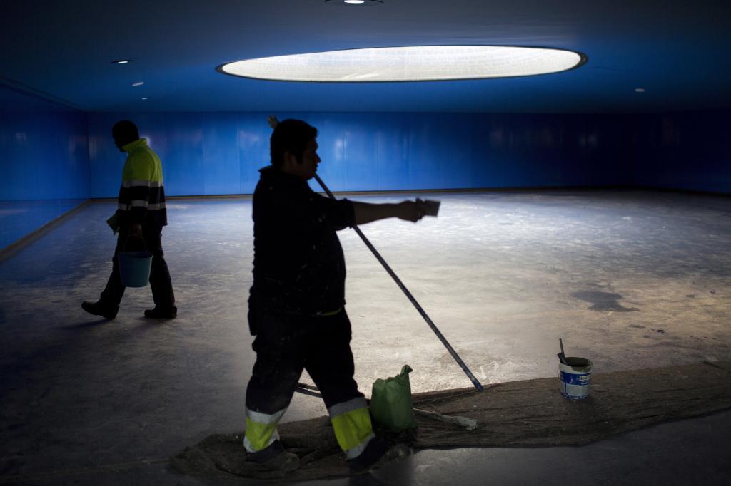 Dos pintores pintan las paredes del monumento del 11-M en Atocha