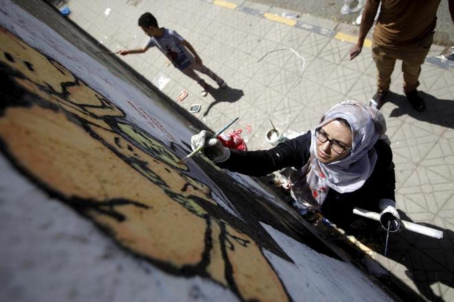 La artista pintando un mural en Saná, Yemen.