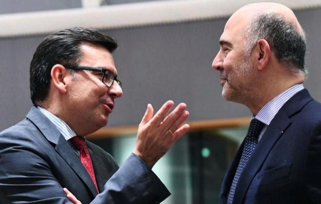 Román Escolano (i) habla en el Eurogrupo de ayer con el comisario Pierre Moscovici.