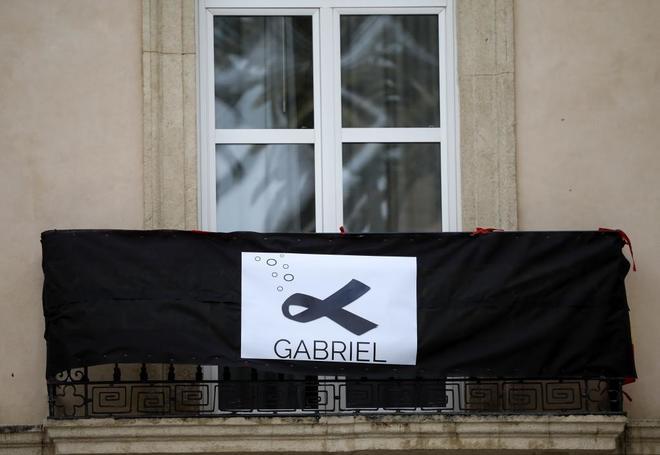 Un lazo negro en forma de pez ilustra una lona colgada en una balcón,...