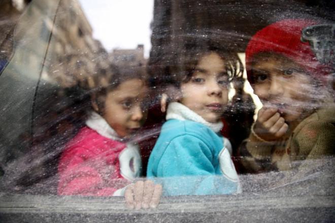 Niños sirios miran desde la ventana de un autobús mientras son evacuados de la asediada Duma.