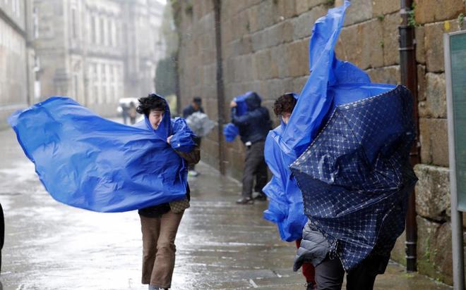 Turistas se enfrentan al viento en Santiago de Compostela.