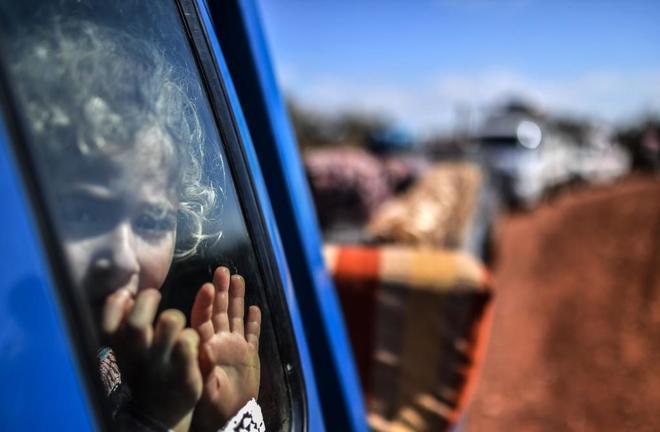 Una niña siria mira a través de la ventanada de un coche, en el checkpoint de Anab.