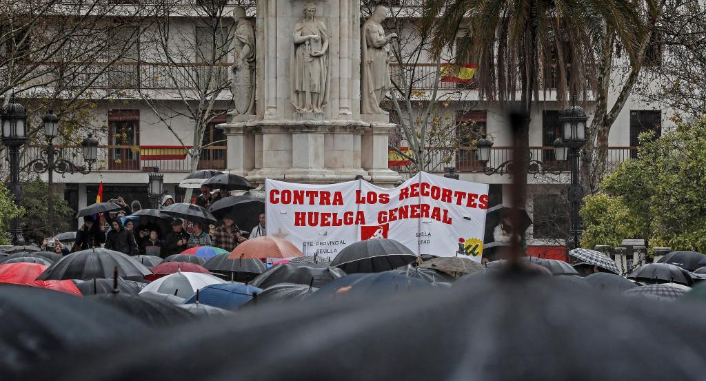 Concentración por la subida de las pensiones en la Plaza Nueva de Sevilla, bajo la lluvia.