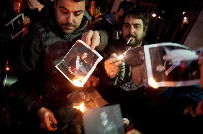 Dos manifestantes queman fotos del Rey Felipe VI, ayer, en Gerona.