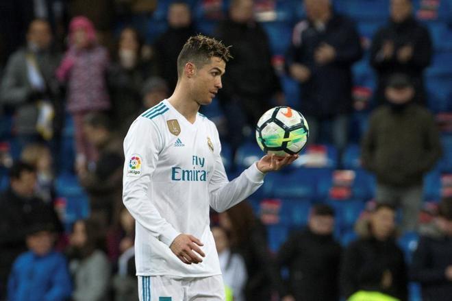 Cristiano Ronaldo sostiene el balón de su póquer ante el Girona.