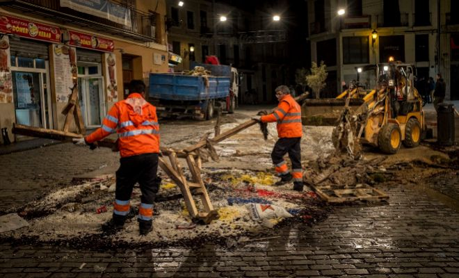 Dos operarios de limpieza del Ayuntamiento de Valencia retiran los restos de una falla tras la 'cremà'.
