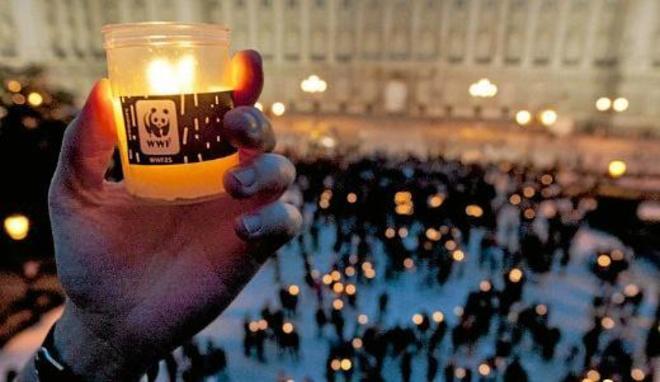 Una mano sostiene una vela en la Hora del Planeta del año pasado.