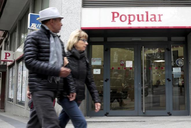 Una pareja pasa ante una oficina de Banco Popular en Madrid.