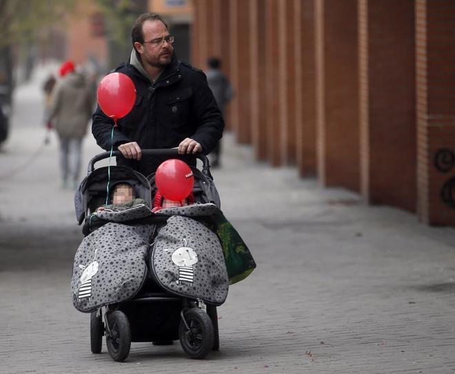 Un padre de familia camina con dos bebés en un carrito en Madrid