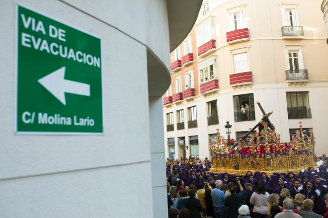 Un cartel avisa de las vías de evacuación durante el paso de una cofradía en Málaga.