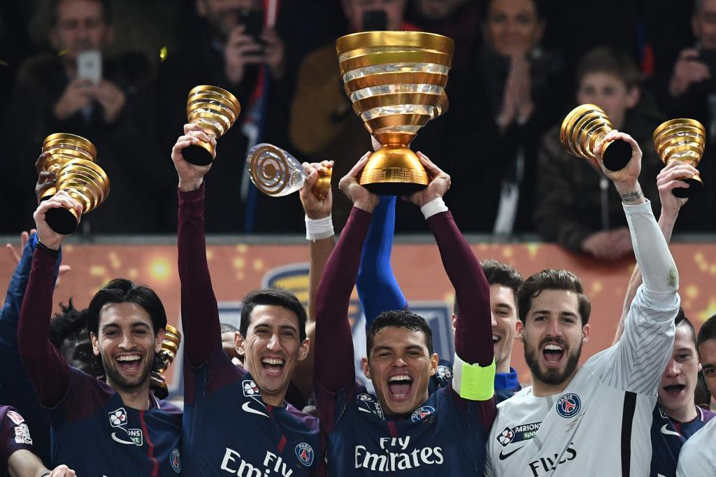 Paris Saint-Germain's Brazilian defender Thiago Silva (C) holds the trophy as he celebrates with teammates German goalkeeper Kevin Trapp (R), Argentinian forward Angel Di Maria (2L) and Argentinian midfielder Javier Pastore (L) after victory in the French League Cup final football match between Monaco (ASM) and Paris Saint-Germain (PSG) at The Matmut Atlantique Stadium in Bordeaux, southwestern France on March 31, 2018. / AFP PHOTO / FRANCK FIFE