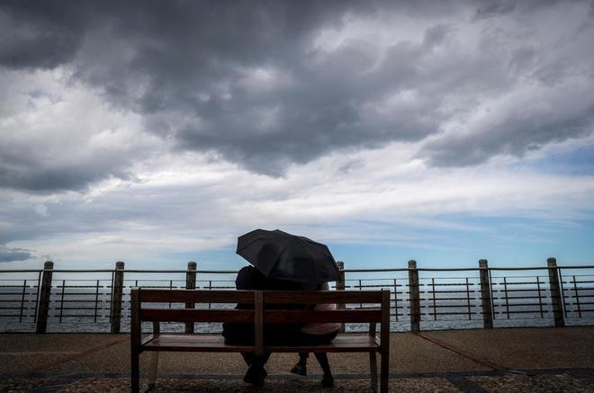 Una pareja descansa en un banco bajo un paraguas en el Paseo Nuevo de San Sebastián.