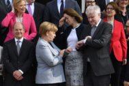 La canciller Angela Merkel y el ministro del Interior Horst Seehofer miran sus relojes junto a Katarina Barley.