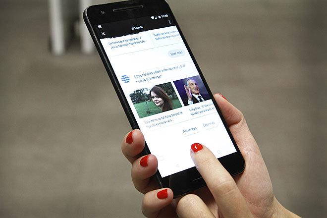 Una usuaria consulta la aplicación de EL MUNDO en su móvil.