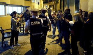 Agentes de los Mossos d'Esquadra, aplaudidos por un grupo de personas...